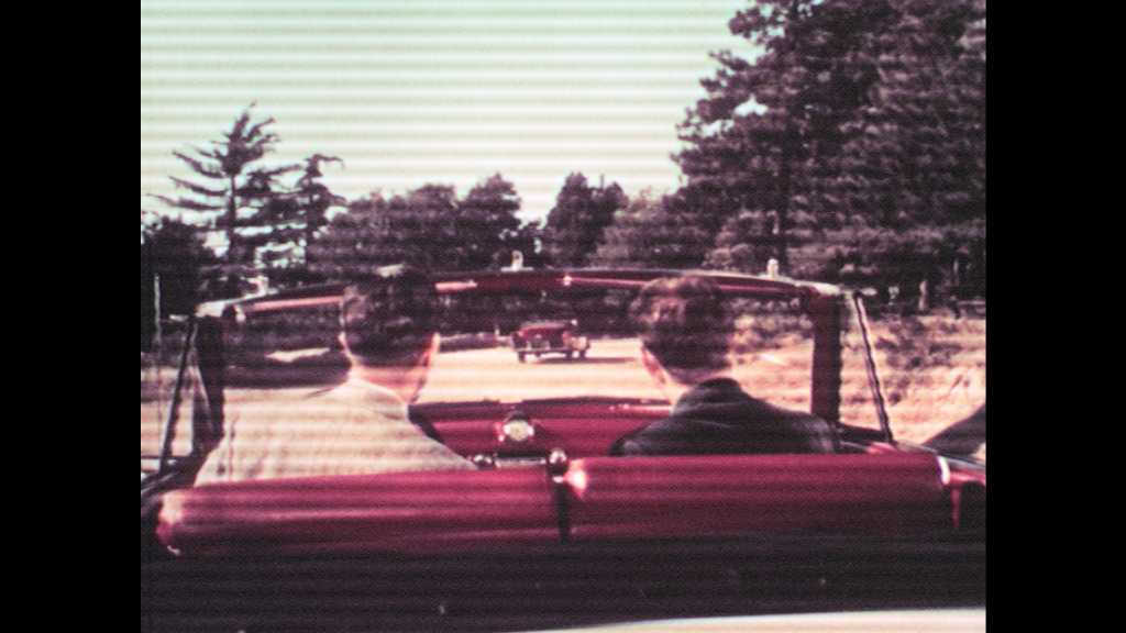 1950s: UNITED STATES: men sit in car. Rear view of open top car. Lady climbs into car. Men get into car. Film set.