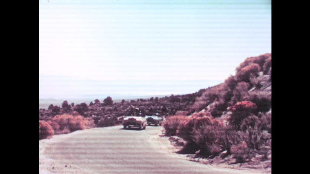 1950s: Cars drive up road in hills. Man and woman smile and talk in car. Woman rolls eyes and smiles.