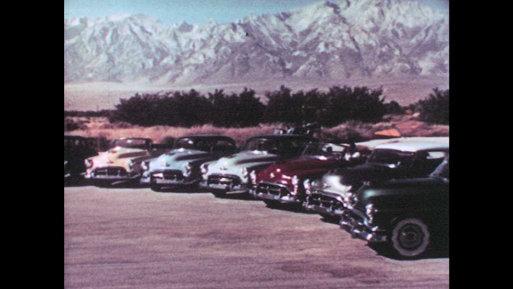 1950s: Brand new Oldsmobile 98 cars pull out one by one.