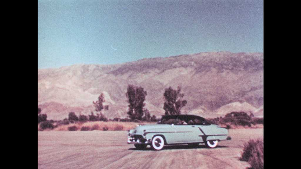 1950s: Brand new Oldsmobile 98 cars drive in a line as a helicopter hovers overhead.