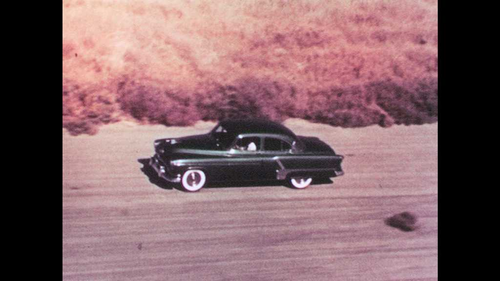 1950s: Brand new Oldsmobile green car drives alongside desert mountains. Silver car with white roof drives and seen from above.