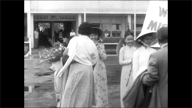 """1950s: Marian Anderson holds flowers, hugs children with conical hats, shakes hands, """"Welcome to Vietnam"""" banner. Flags outside Saigon Airport. Bangkok, two story building with porches."""