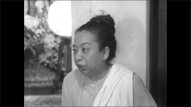 1950s: Marian Anderson and Asian woman sit down inside Buddhist temple, talk.