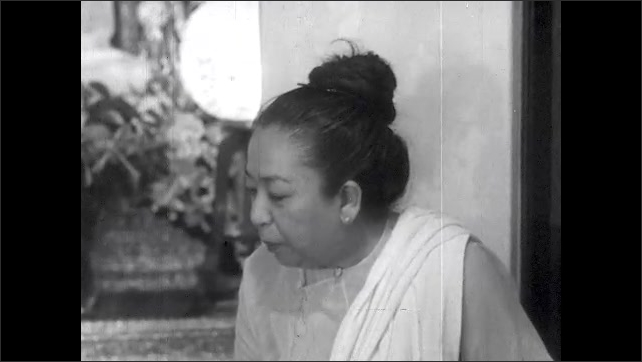 1950s: Marian Anderson and Asian woman sit inside Buddhist temple, talk.