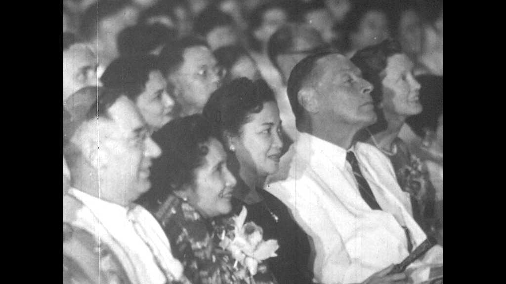 1950s: People sit in audience, word Manila appears on screen. Marian Anderson and man in uniform carry large floral wreath, set it down in from of memorial.