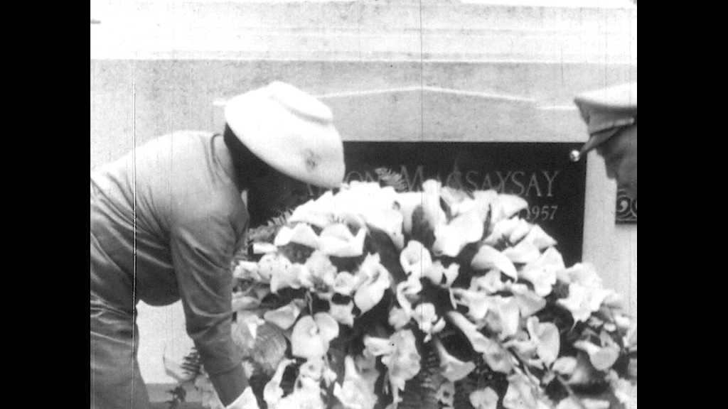 1950s: Marian Anderson and man in uniform set floral wreath down on memorial. Headstone plaque for Ramon Magsaysay. Marian sings.