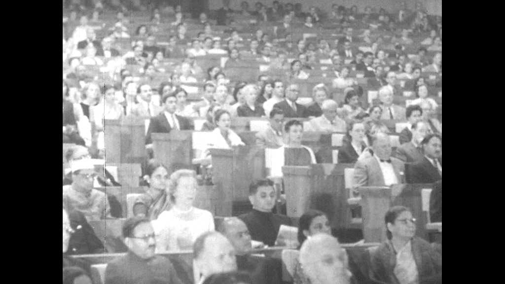 1950s: People sit in audience, word New Delhi appears on screen. Prime Minister Nehru sits in audience.