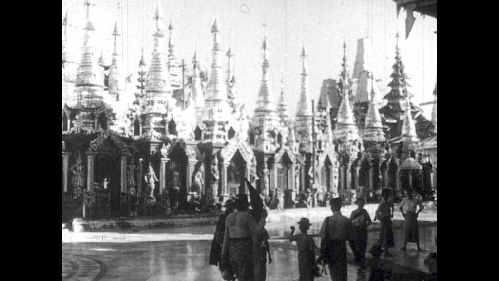 1950s: People walk around the Yangon in Myanmar. Audience sits in auditorium.