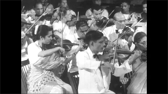 1950s: UNITED STATES: Sailors play in Indian navy. Man plays clarinet. String section of orchestra. Ladies play violins