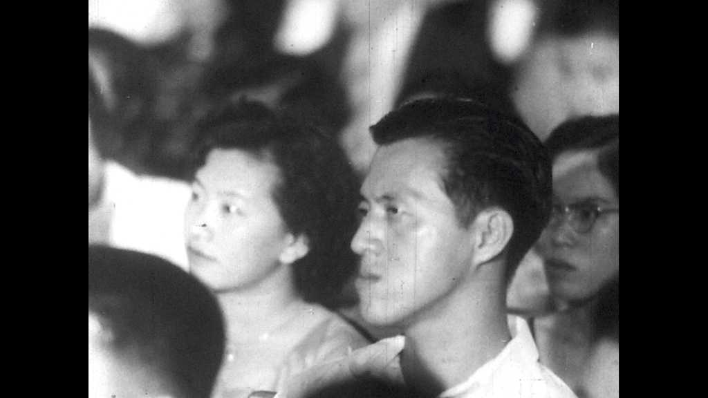 1950s: UNITED STATES: man in audience listens. Lady stares. Audience watches concert. Lady sings on stage