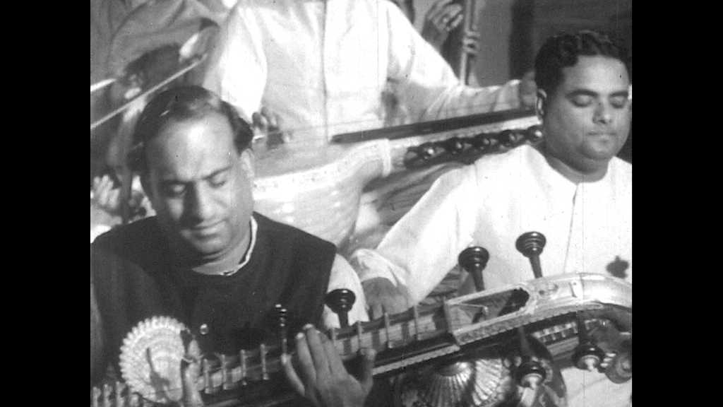 1950s: UNITED STATES: men play sitars in band. Musicians play in hall. Conductor instructs musicians