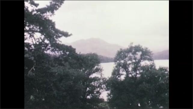 1940s: View of hills. Long shot of lake. View of lake shore.