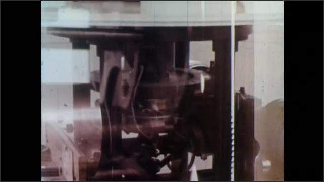 1970s: Close up tilt up part of lighthouse, double exposure of gears turning. Close up of light rotating.