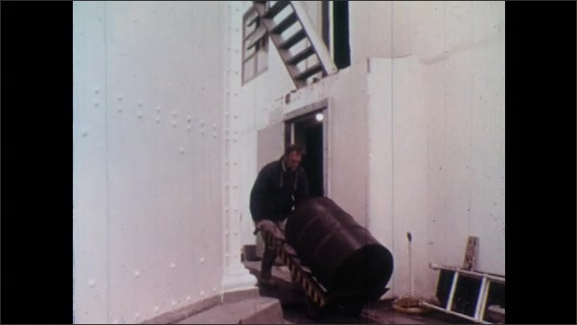 1970s: Tracking shot of boat, driving away from lighthouse, flag in foreground. Man pushing barrel, girl walks up stairs in background. Girl walks up stairs.