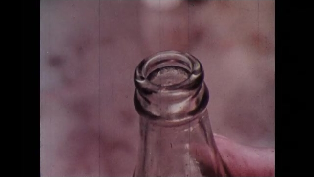 1970s: Hand writing on paper. Hand puts paper and cork in bottle. Hand puts paper in bottle. Close up of man. Man and girl walking with bottles.