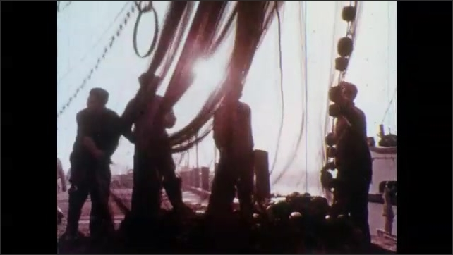 1970s: Bottle floating in water. View of water. Close up of girl's eyes. Men pulling up net. Pan of crane lifting bucket, man in foreground.