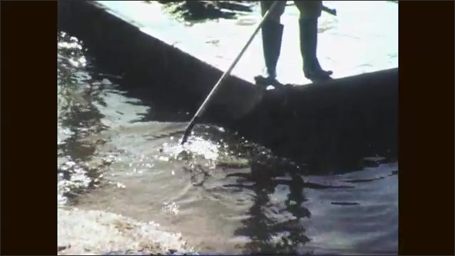 1960s: Derelict building. Men rake bottom of waterway for junk and remove it to barge.