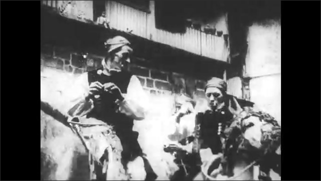 SPAIN 1930s: Men sit on horses. Chicken hangs by feet from rope. Crowd gathers on sides of street.