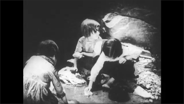 SPAIN 1930s: Woman washes child's head in river. Children place chunks of bread into water, eat bread.