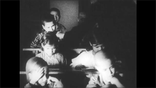 SPAIN 1930s: Students sit at desks. Man places books in front of students, opens books. Students swings legs back and forth under desk.