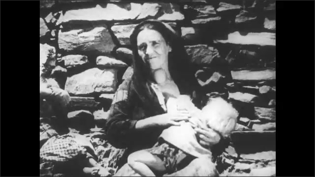SPAIN 1930s: Man holds child's hand, walks down street. Woman sits outside, breastfeeds child, adjusts child in lap. Stone wall.