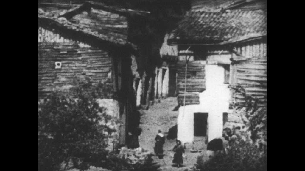 SPAIN 1930s: People walk around village streets. People ride and walk horses down alleyway. Buildings.