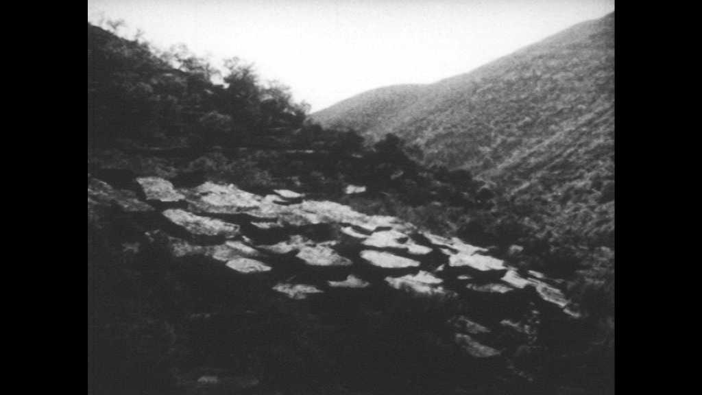 SPAIN 1930s: Rocky mountainside. Woman holds child, stands in front of rocks. Women walk with children through village.