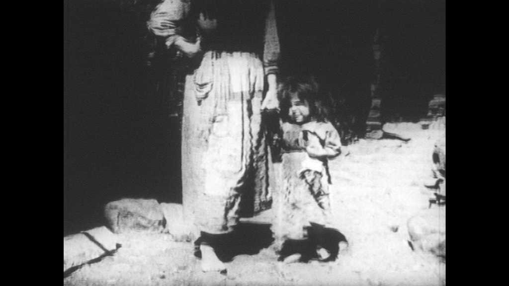 SPAIN 1930s: Woman holds child's hand, walks through village. Pig roots. Man holds child on lap. Children and old woman stands against wall.