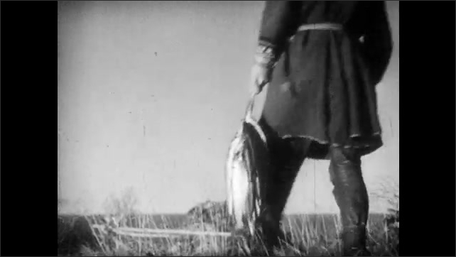 1950s: FINLAND, EUROPE: nomad man catches fish. Fish in net. Close up of man's face. Boys walk home with wish. Snow covered mountain