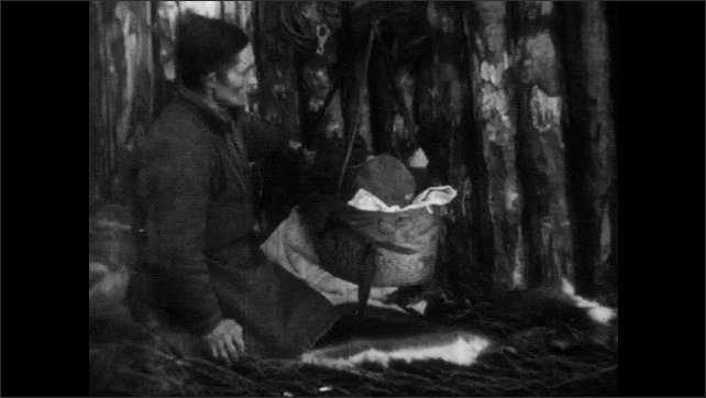 1950s: FINLAND, EUROPE: family work by fire. Man rocks baby in cradle. Nomadic family at home