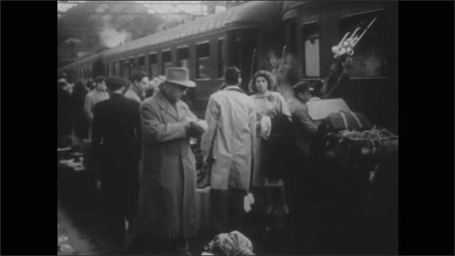 1960s: Train schedule board. Train pulls into station. People disembark train. Man helps woman off train.
