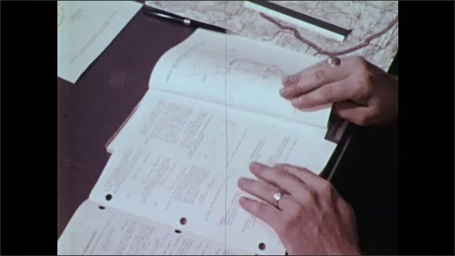 1970s: UNITED STATES: man reads bulletin and technical manual on safety guidelines. Man draws line on paper.