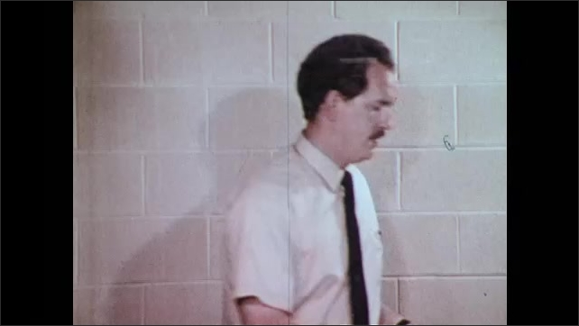 1970s: UNITED STATES: man calculates safety ratios in office. Man walks along corridor.