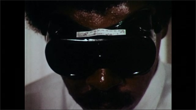 1970s: UNITED STATES: man wears safety goggles. Close up of man wearing goggles. Label on eye wear. Argon laser goggles