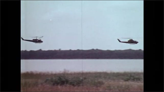 1970s: UNITED STATES: Helicopters fly over ground. Helicopters fly in tandem.