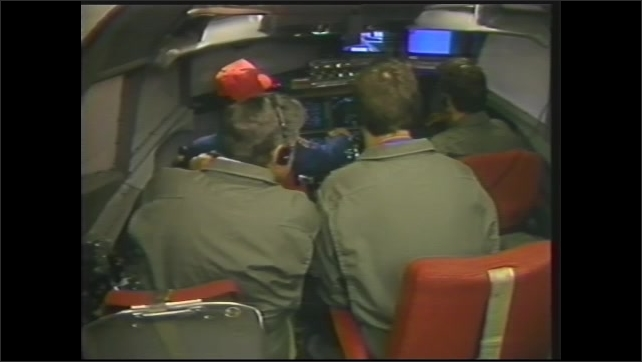 1990s: Pilots sit in cockpit of plane and speak into headsets. Airmen fly plane from simulation cockpit in rear. Hands operate flight controls, Men pilot craft from secondary cockpit.