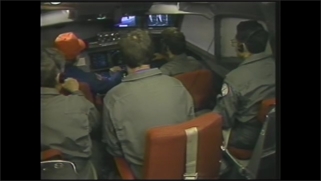 1990s: Men and women work at computer consoles on laboratory plane. Fingers point to monitor. Airmen fly plane from simulation cockpit in rear.