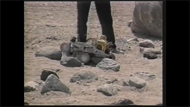 1990s: Automated micro rover rolls over simulated surface of Mars. Man stands near micro rover.