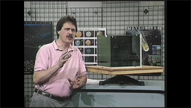 1990s: Man leans on counter near mirrors and speaks.