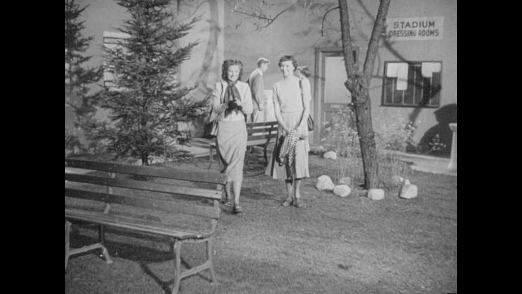 1940s: Girls talking. View over girl's shoulder, girl talking. Girl talking.