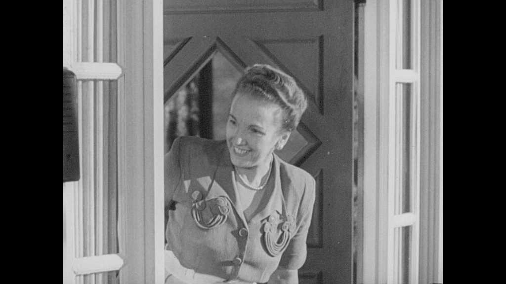 1940s: Woman talking in doorway. Boy and girl on porch, walk into house, close door. Dissolve, boy approaches door, rings doorbell.