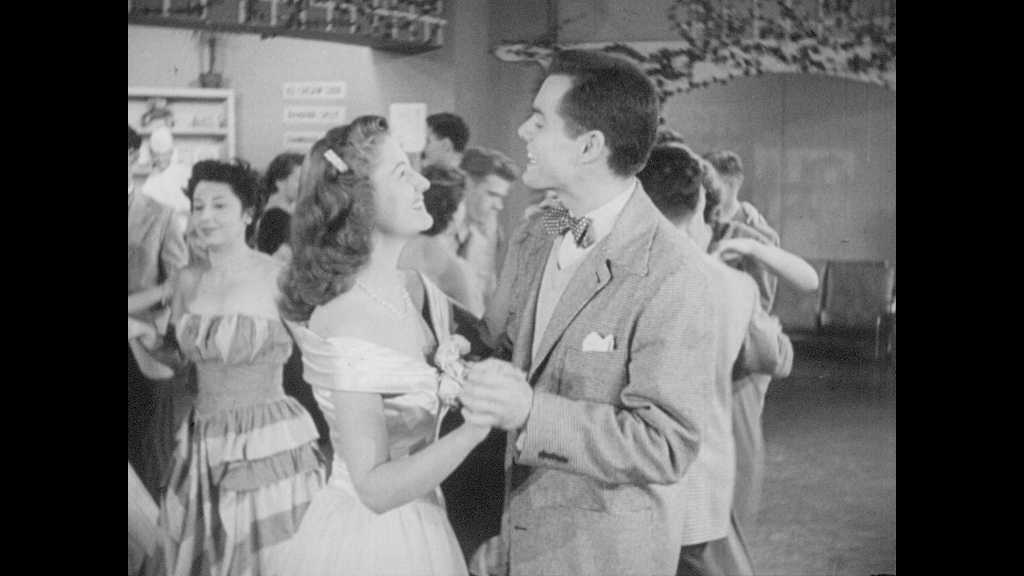 1940s: UNITED STATES: man dances with lady at ball. Couples on dance floor. Man smiles at lady. Girl looks across room. Man stands at entrance