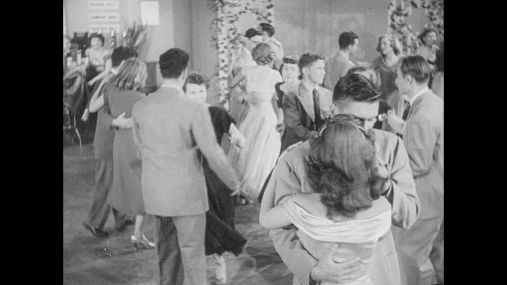 1940s: UNITED STATES: girl dances with boy. Couples on dance floor. Lady nods at man. Couple leave dance.