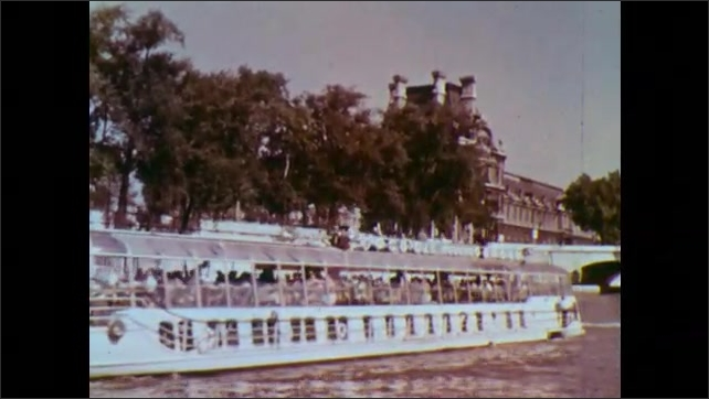 1960s: FRANCE: EUROPE: Bridge over river. Boat with passengers on the Seine. Passengers on boat. People on deck of boat.