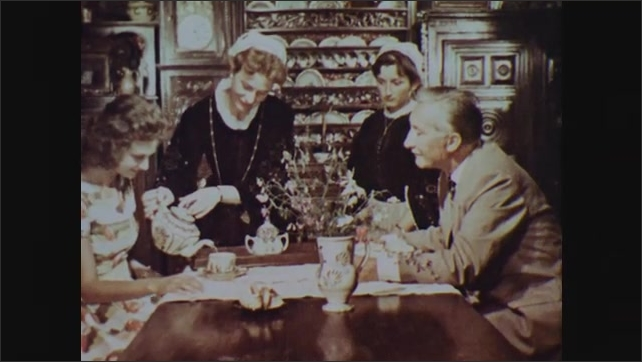 1960s: Servers place tea set and plates on table. Woman in period dress pours tea for couple in booth.