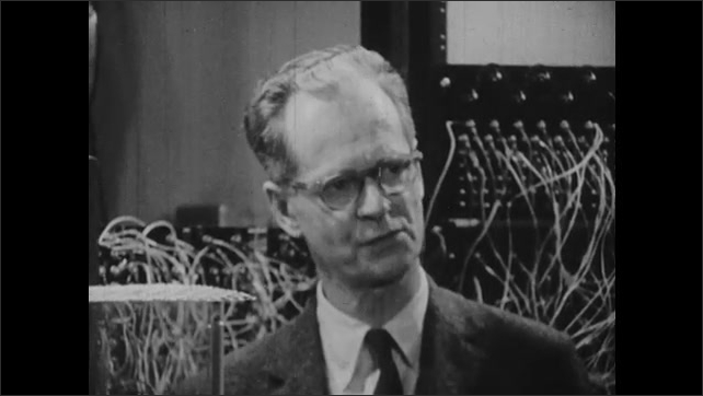 1950s: Close up of B. F. Skinner talking. Man by pigeon in cage.
