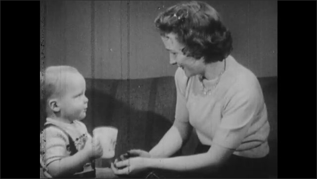 1950s: Woman with glass speaks to child. Child responds. Woman gives drink of water to toddler. Woman smiles. Toddler drinks water from glass near couch.