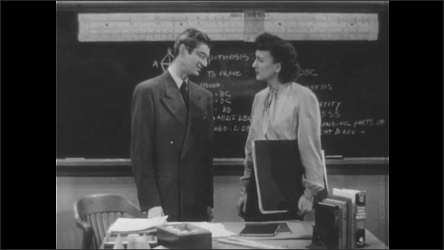 1940s: UNITED STATES: lady talks to math teacher by chalk board. Man points with pencil. Students sit in classroom.