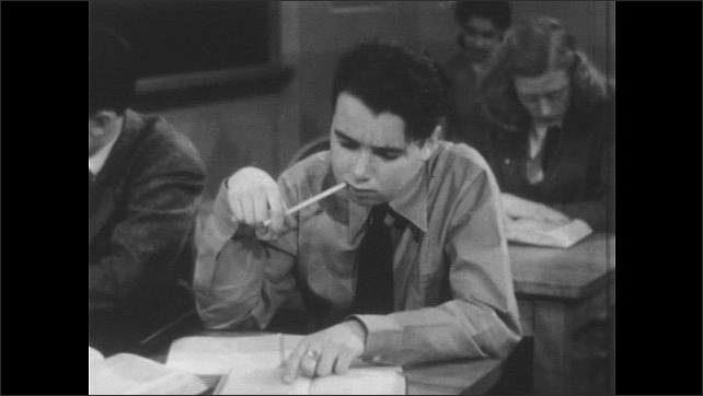 1940s: UNITED STATES: teacher stands and thinks in classroom. Teacher looks at notes. Boy works at desk. Boy writes notes