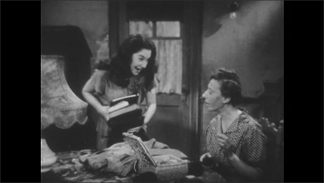 1940s: UNITED STATES: girl smiles at mother in room. Girl picks up things from table. Lady sews fabric